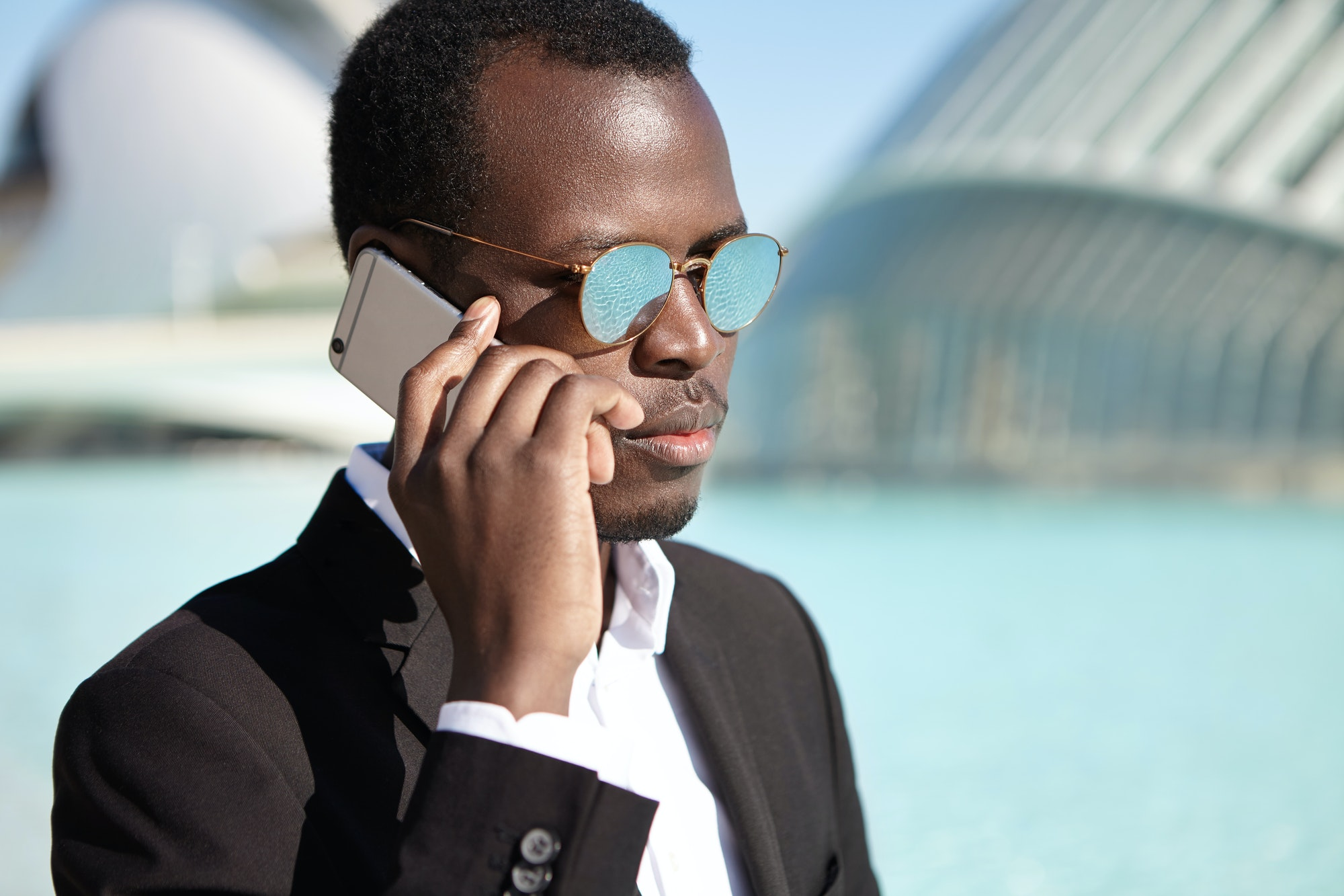 People, lifestyle, business and modern technology. Confident Afro American businessman wearing black